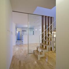 白を基調/繋がる家 中庭 将来分割できる子供室 階段室からダイニング-キッチンー内玄関を…