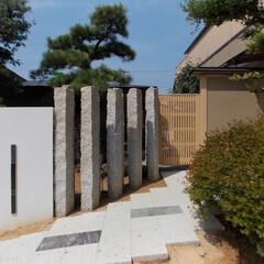 深岩石/石柱/木製格子戸 深岩石の床と錆石の石柱と木製格子門扉