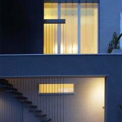 鋼棒/鋼棒吊り鉄骨階段/2世帯住宅/プロフィリットガラス/フェイジョアノキ/ギンバイカ 須賀町の家外観夜景。2世帯住宅の2つのア…