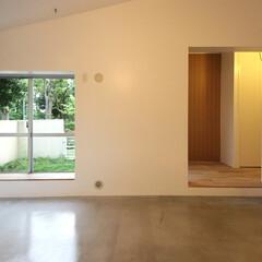 個人邸リノベーション モルタル床のリビングルーム越しの、オーク…