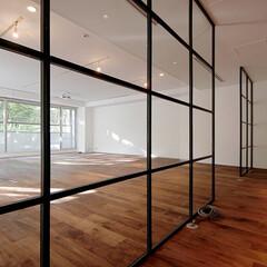 オフィスリノベーション スチール格子戸で仕切られた廊下とワークス…