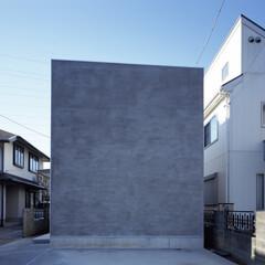 横浜/モルタル/キューブ 窓のないファサードの手前は駐車場。