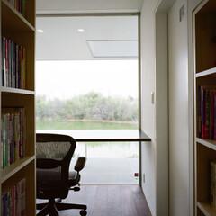 書斎/借景/本棚 1階の本棚に囲まれた廊下の先には、池を望…