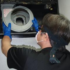 人物写真 台所換気扇分解清掃中の写真です。