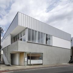 無垢材/シンプル コンクリートの上に漆喰と金属板の外壁