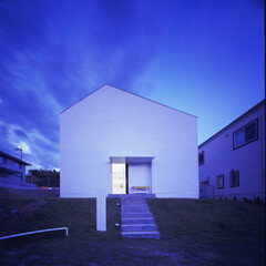 家型/白い家/中庭 寿命のあるコンクリートの擁壁を設けず、芝…