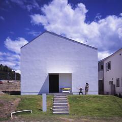 中庭/家型/塗り壁/芝生 計画地は西側の道路に面し、周囲は隣家に囲…