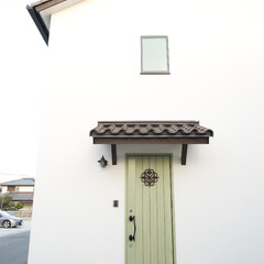 三角屋根/しっくい/庇/玄関ドア 外壁もしっくい塗り壁。緑のドアがアクセン…