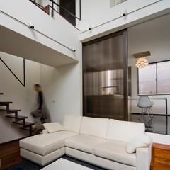 リビング/吹抜け/ブリッジ/リビング階段 白と黒、ブラウンのカリン材からなる内装は…