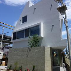 店舗/二世帯住宅/変形敷地/三角形/線路 住宅部分の、 しっとりとした白い壁とは対…