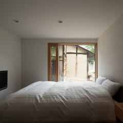 寝室/大きな窓/換気窓/土壁 【おかやまのいえ】 納屋の土壁を借景した…