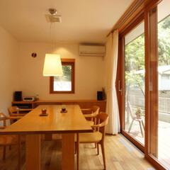 木製サッシ/デッキ/無垢フローリング/無垢のテーブル/漆喰壁 庭に向かって張り出したダイニングルームに…