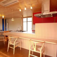 メイプルのカウンター/コルクタイル/パイン材の天井 キッチンの赤いメラミン板に対して、ダイニ…